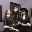 Two people trying on costume in the Baroque gallery