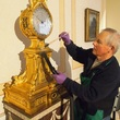 Volunteer conservator cleaning the ormolu sidereal clock