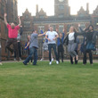 Staff and volunteers jumping in air outside Aston Hall
