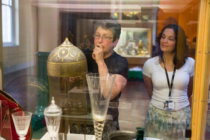 Visitor looking at helmet from Iran