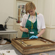 Conservator Emma conserving and treating the frame in the conservation studio