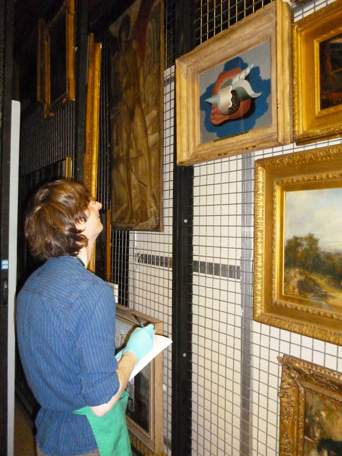 Conservator Ben condition checking artwork in the museum store
