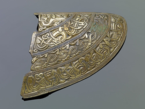 Cheekpiece from the helmet, decorated with a pattern of interlocking creatures.