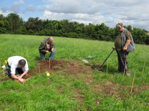 Metal detectorists and archaeologists assessing the field