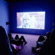 Visitors watching Feed Me by Rachel Maclean, in the I Want! I Want! Art & Technology exhibition