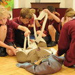 A group of children preparing our Egyptian mummy for the afterlife by wrapping it in bandages, in a school session at Birmingham Museum and Art Gallery