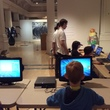 A group of children on computers in a designing computer games workshop