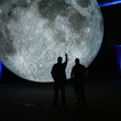 Two visitor silhouetted by the museum of the moon