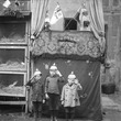 Black and white photo featuring 3 children in front of a puppet show