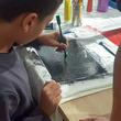 Child creating a print during the mono-print workshop