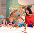 Family viewing the Velociraptor in the Dippy on Tour exhibition at Birmingham Museum and Art Gallery