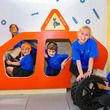 A group of children in a wooden car in the MiniBrum garage workshop