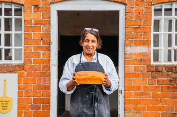 The baker holding a loaf of bread outside Sarehole Mill