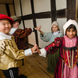 Group of four children dressed in historical costumes and dancing inside Blakesley Hall