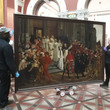 Technicians moving a painting