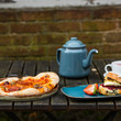Pizza, tea and scones on table in the courtyard at Sarehole Mill